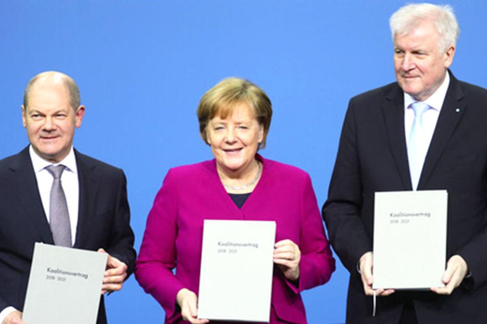 Bundeskanzlerin Angela Merkel (CDU), Mitte), der CSU-Vorsitzende Horst Seehofer (rechts) und der kommissarische SPD-Vorsitzende Olaf Scholz zeigen den unterzeichneten Koalitionsvertrag.