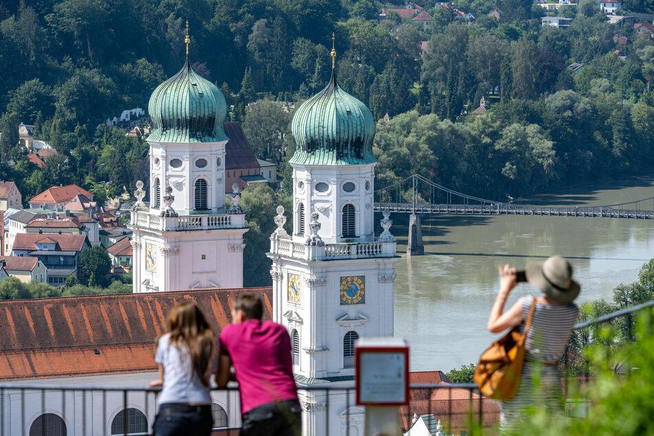 Passau: Touristen stehen bei sommerlichen Temperaturen vor dem Dom St. Stephan (Archivbild). Bayern hatte ein strikte Regelung, was Tourismus im Bundesland betrifft.