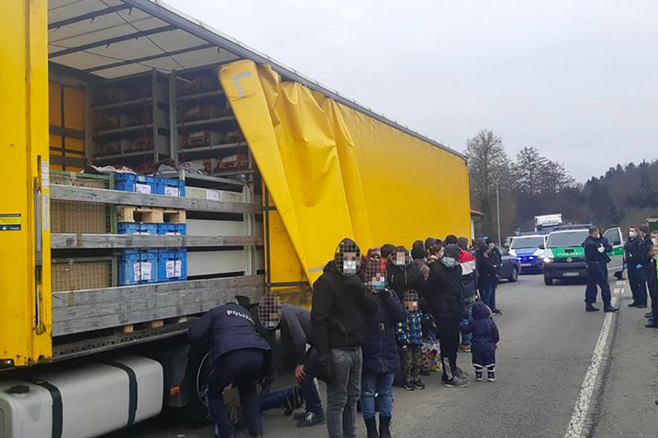 27 geschleuste Menschen stehen vor der Ladefläche eines LKW bei Windorf.