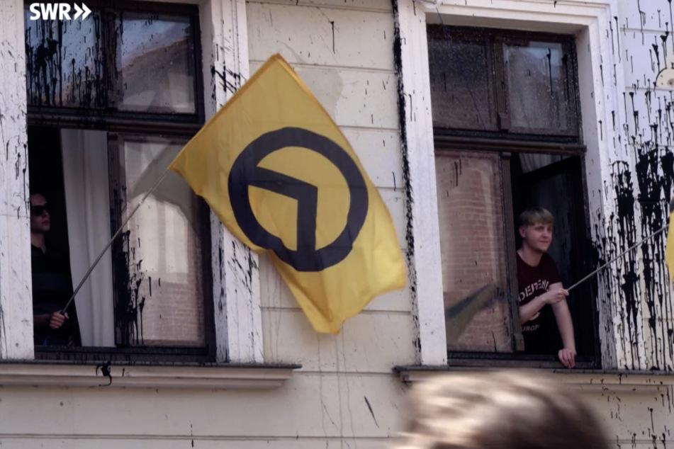 Mitglieder hissen aus dem ehemaligen Haus der Identitären Bewegung in Halle ihre Flagge.