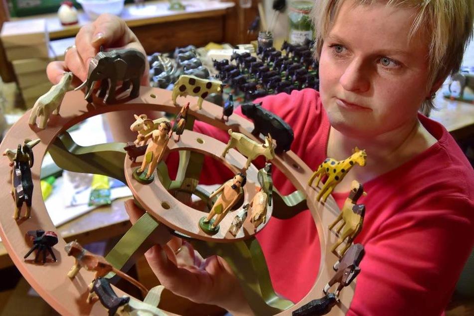 Tabea Drechsel ordnet in der Seiffener Werkstatt Werner Figuren auf einer Leuchteretage an.