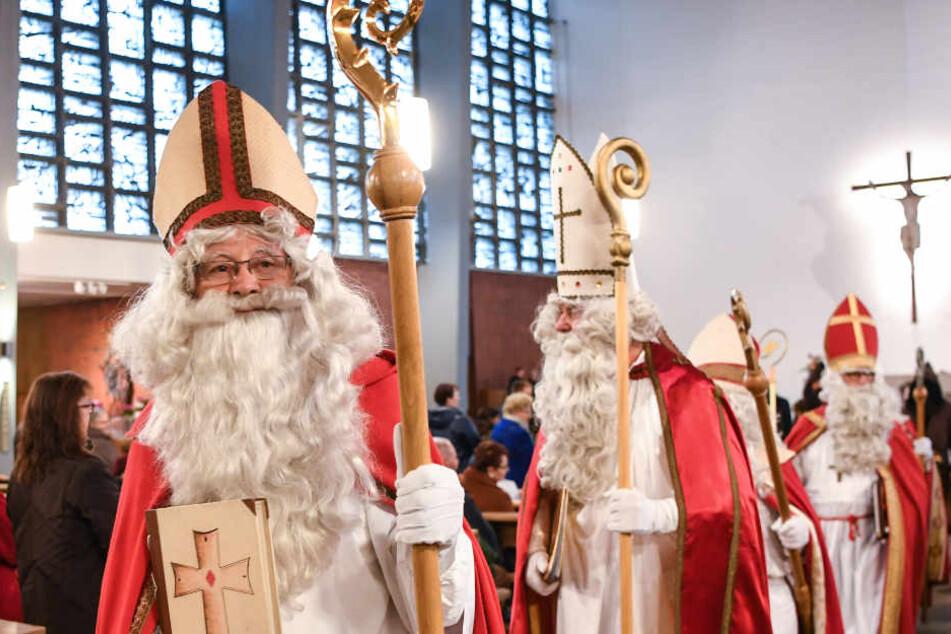 Sechs verkleidete Nikoläuse ziehen aus der Kirche aus.