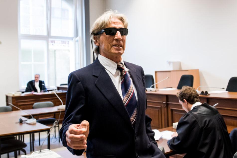 Der Angeklagte steht mit Sonnenbrille auf der Nase und im Anzug im Gerichtssaal.