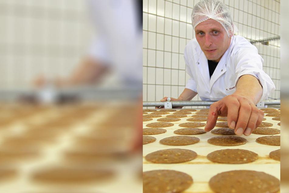 Ein Mitarbeiter der Lebkuchenfabrik Ferdinand Wolff GmbH in Nürnberg entnimmt zu Kontroll-Zwecken noch nicht gebackene Oblaten-Lebkuchen vom Förderband.