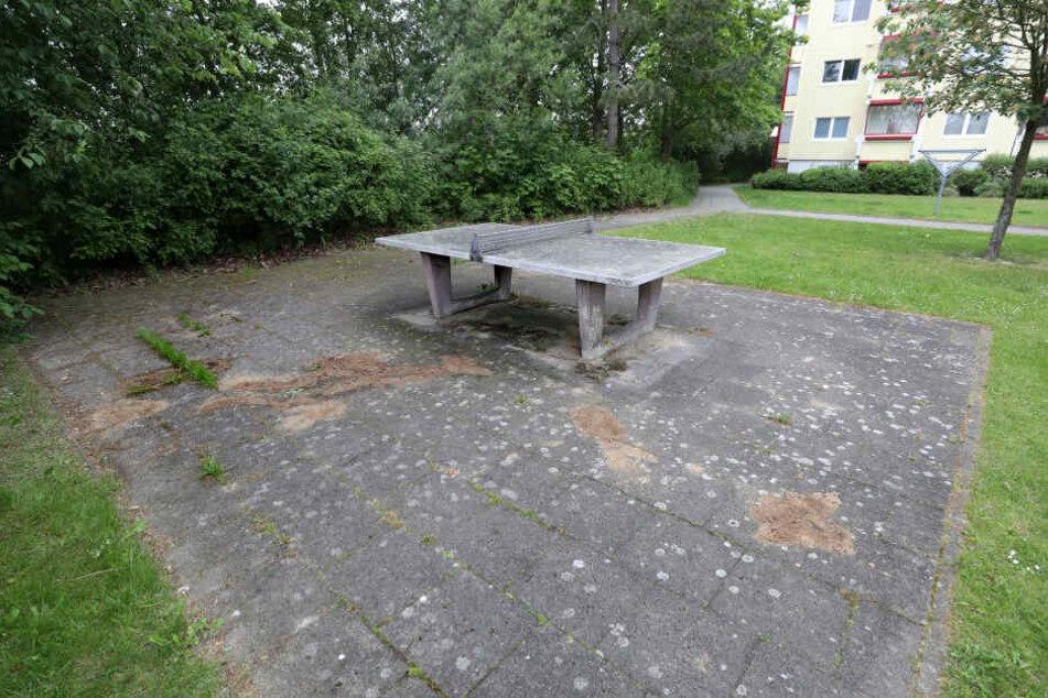 Auf einem Spielplatz unweit der Fundstelle eines toten Säuglings sind dunkle Stellen mit Sand abgedeckt, zuvor hat die Polizei die Spuren gesichert.