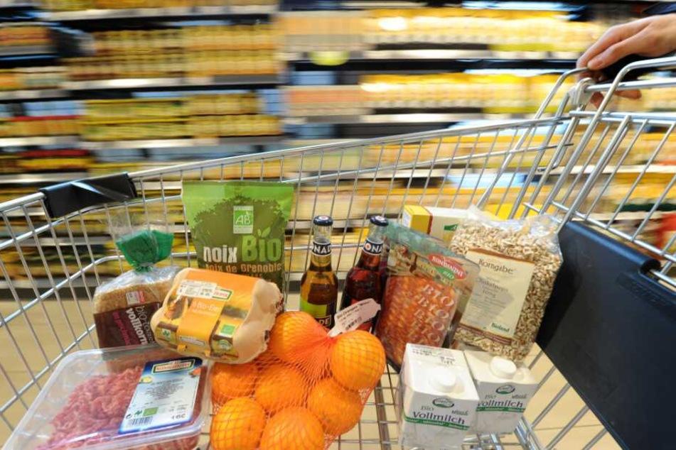 Ein Einkaufswagen mit verschiedenen Bio-Produkten wird durch einen Biomarkt geschoben