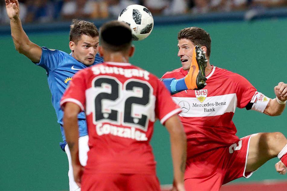 Der Rostocker Julian Riedel (links) und der Stuttgarter Mario Gomez (rechts) im Zweikampf, der Stuttgarter Nicolas Gonzalez (Mitte) verfolgt die Szene.