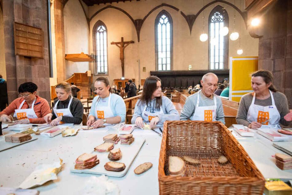 Freiwillige Helfer schmieren Brote für die Bedürftigen.