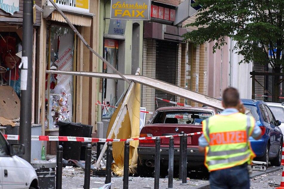 Am 9. Juni 2004 sichert ein Polizist die Spuren der Explosion in der Keupstraße im Stadtteil Mülheim. 17 Jahre sind seither vergangen. Nun soll es ein Denkmal geben.