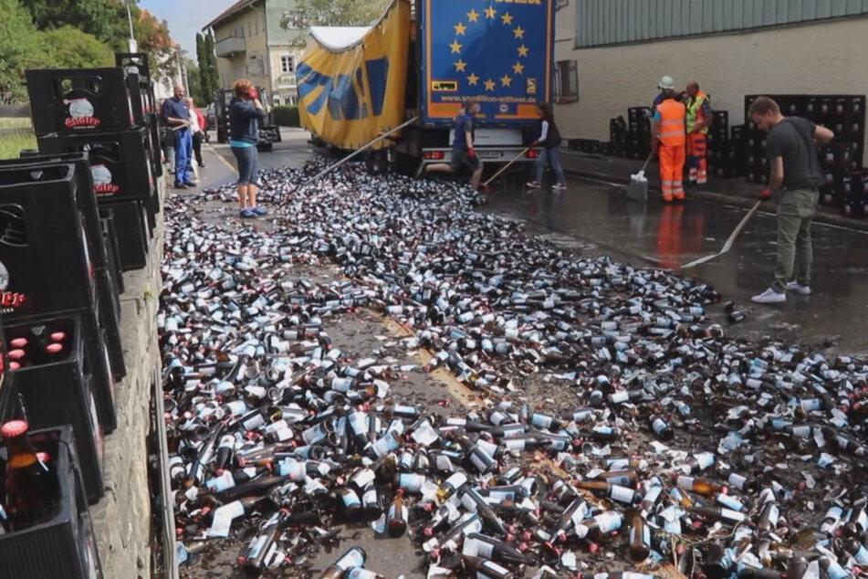 Einsatzkräfte von der Feuerwehr sowie Helfer räumen zahlreiche zerbrochene Bierflaschen auf.