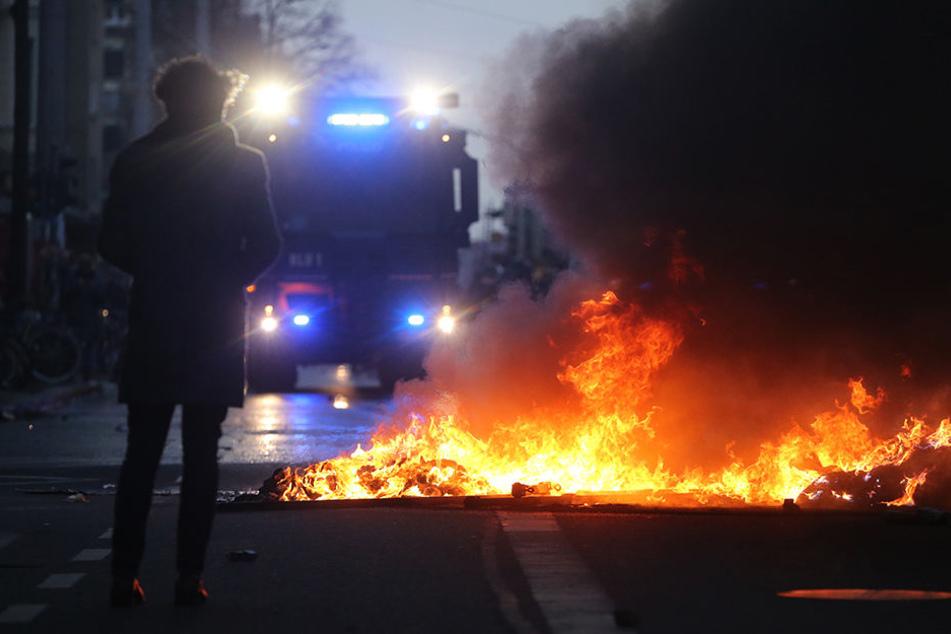 Ein Wasserwerfer steht am 12. Dezember 2015 vor einer brennenden Barrikade in Leipzigs Südvorstadt. Der Randale-Schaden ging damals in die Hunderttausende.