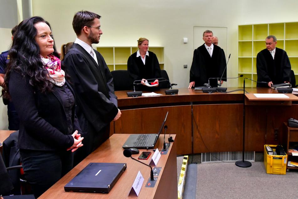 Die Angeklagte Zschäpe steht 2018 neben ihrem Anwalt Mathias Grasel während der Vorsitzende Richter Götzl (2.v.r.)und die Vertreter des Staatsschutzsenats Feistkorn (l), Lang (2.v.l.)und Kuchenbauer (2.v.r) den Gerichtssaal betreten.