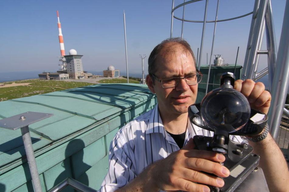 Wetterbeobachter Michael Wellmann liest auf dem Dach der Wetterwarte Brocken den Sonnenscheinautographen ab.