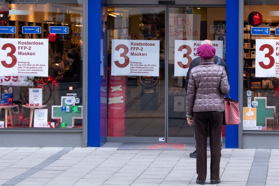 Kunden warten vor einer Apotheke.