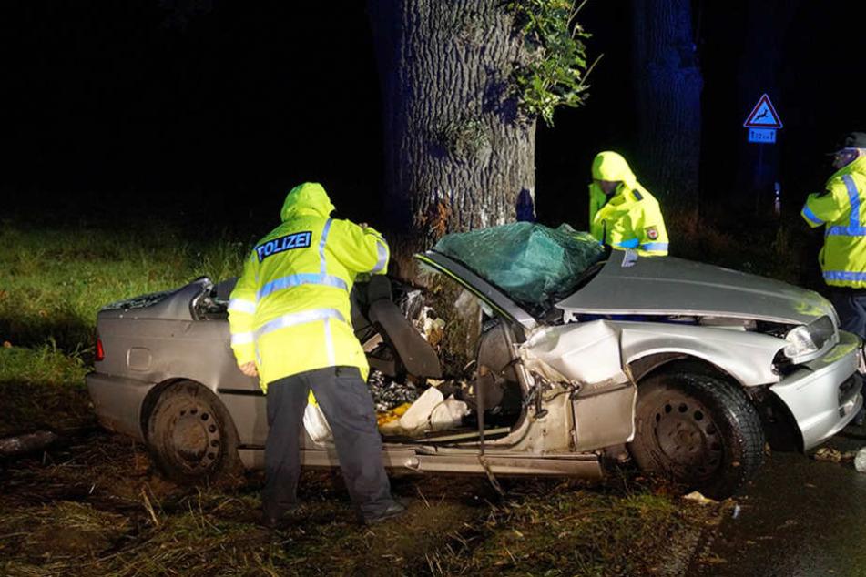 Polizeibeamte untersuchen in der Nacht das Wrack des verunglückten BMWs.
