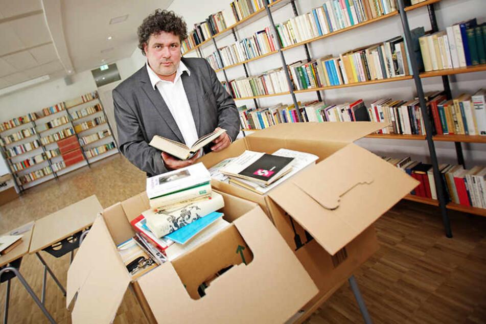 Jürgen Küfner (51), Direktor der Volkshochschule Dresden, zeigt einige der 13.000 geschenkten Bücher.