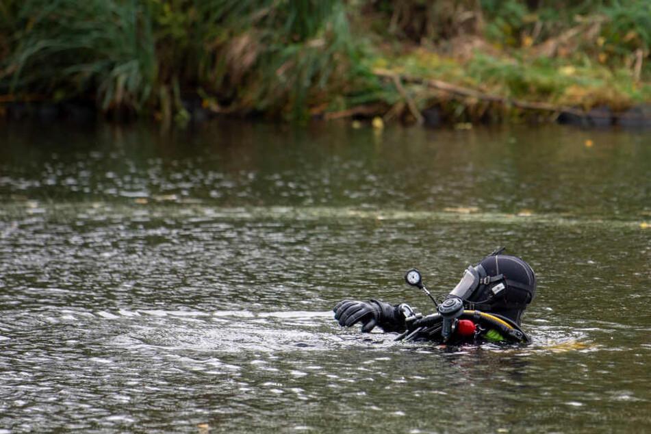 Ein Taucher der Feuerwehr sucht einen See nach Hinweisen ab. (Symbolbild)