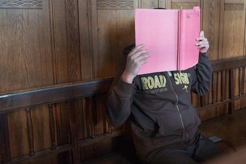 Der Angeklagte verbarg sein Gesicht hinter einen Aktenhefter.