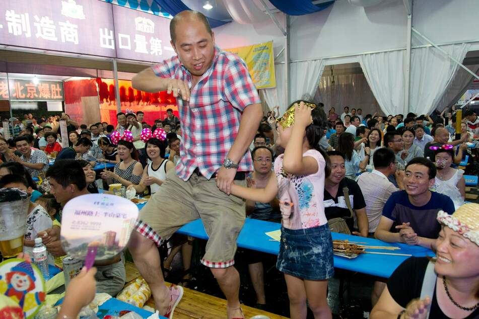 Ein Besucher tanzt beim Oktoberfest im chinesischen Qingdao in einem Festzelt auf einer Biertischgarnitur. (Archivbild)