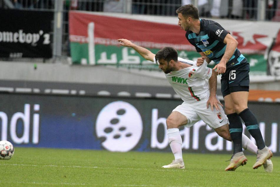 Jan Moravek (l) von Augsburg und Marko Grujic von Berlin kämpfen um den Ball.