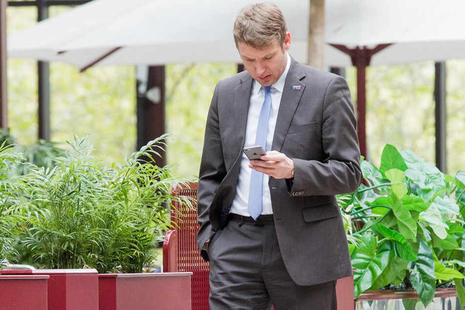 Normales Bild: André Poggenburg mit seinem Smartphone.