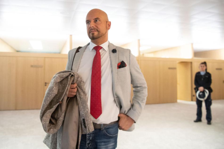 Stefan Räpple, Landtagsabgeordneter der AfD, steht außerhalb des Planeralsaals, im Hintergrund steht eine Polizistin.