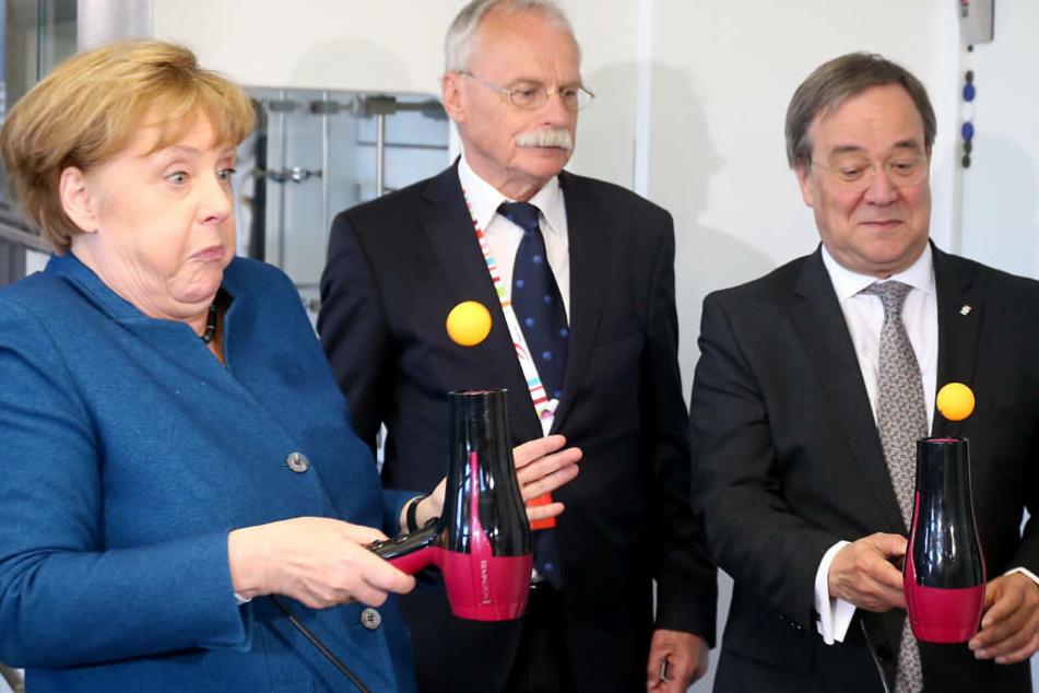 Bundeskanzlerin Angela Merkel (li.) und NRW-Ministerpräsident Armin Laschet (re.) machen ein Experiment zum Bernoulli Effekt und jonglieren einen Tischtennis Ball auf einem Föhn. Uni-Gründer Ernst-Andreas Ziegler (mi.) schaut interessiert zu.