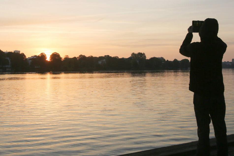 Ein junger Mann fotografiert den Sonnenaufgang an der Außenalster.