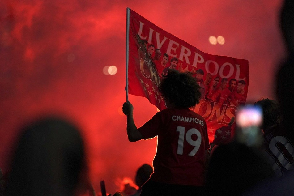 Fans des FC Liverpool feiern vor dem Stadion an der Anfield Road, nachdem ihre Mannschaft nach der 1:2-Niederlage von Manchester City gegen Chelsea als Meister der Premier League feststeht.