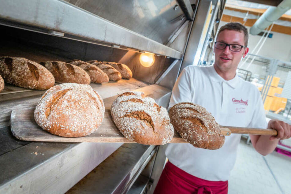 Bäcker David Böhme (29) holt die frischgebackenen Bier-Brote in der Bäckerei Groschupf aus dem Ofen.
