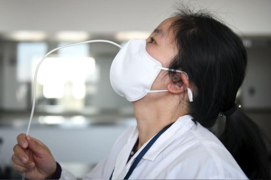 Kampf gegen das Coronavirus: Prüfer testen in einem Labor des Shaanxi-Instituts für die Qualitätsüberwachung von Medizinprodukten die Dichtheit einer Schutzmaske.