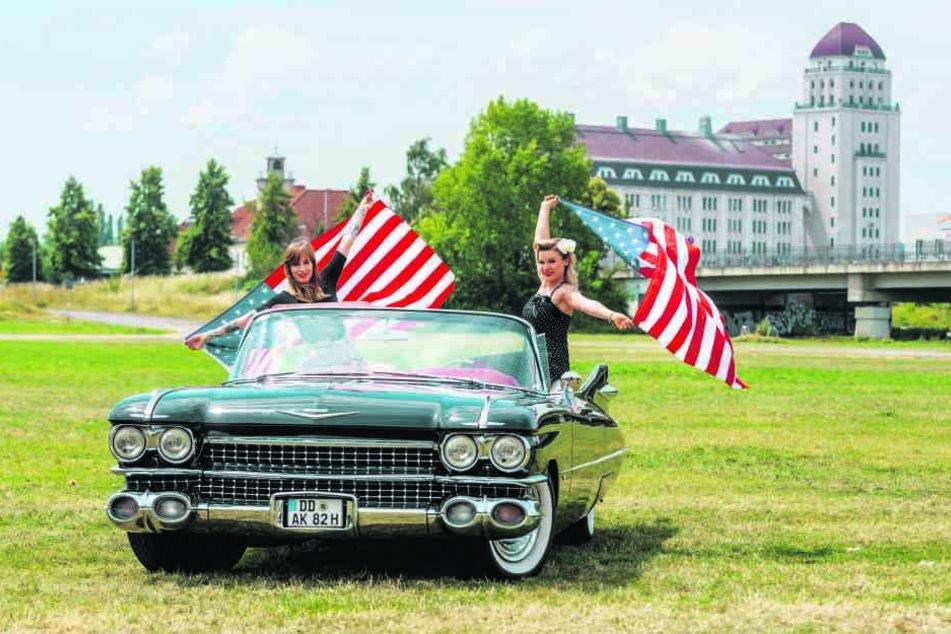 """Drei Mädels: Sarah 28, (l.) und Katja (28) schwenken in Cadillac-Lady """"Christine"""" die amerikanische Flagge."""