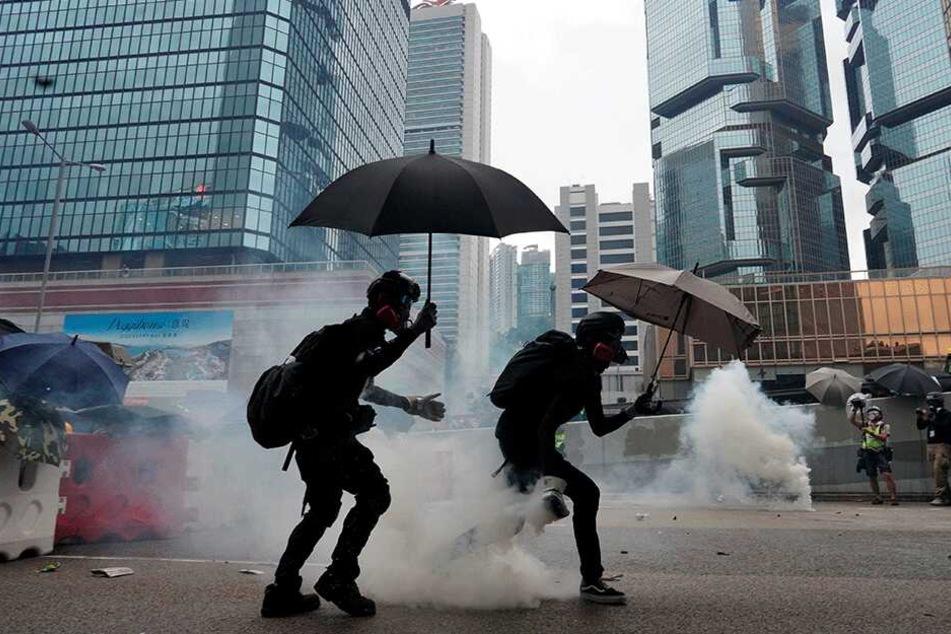 Demonstranten gehen vor explodierenden Tränengasgranaten in Deckung, die von der Polizei abgefeuert werden.