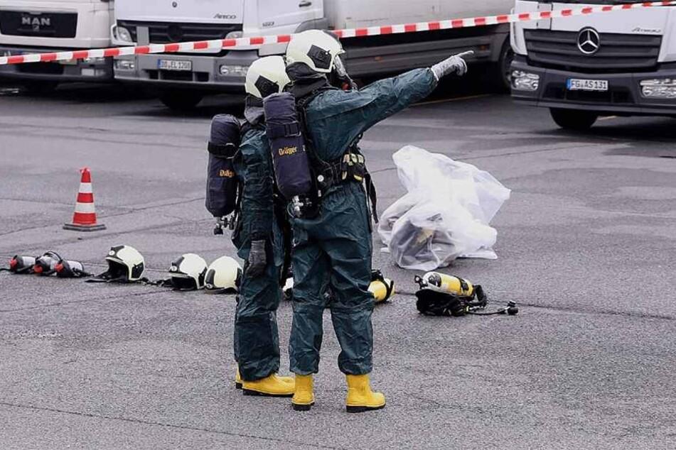 Zwei Feuerwehrmänner mit Schutzanzügen an der Einsatzstelle.