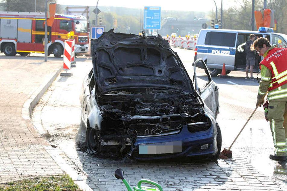 Der Mercedes brannte komplett aus. Ein Mitarbeiter der Feuerwehr versucht hier, die Spuren des Löschens zu beseitigen.