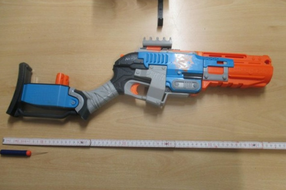 Das Spielzeuggewehr und eines der Geschosse.