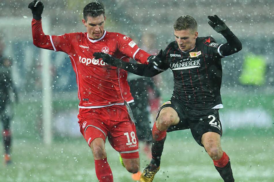 Christoph Moritz (l) will Unions Grischa Prömel im Schneegestöber den Ball abnehmen.