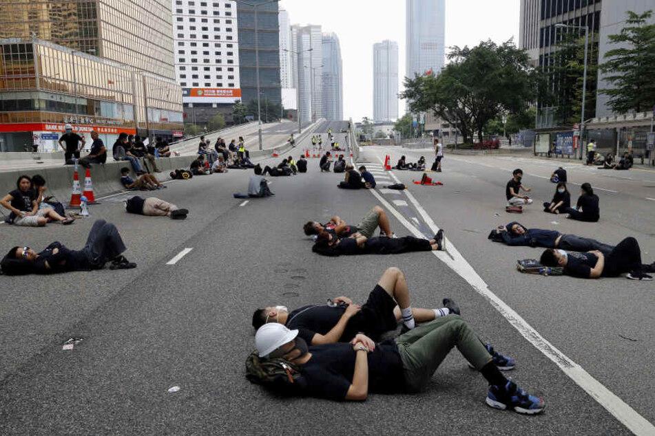 Demonstranten, die über Nacht unterwegs waren, liegen auf einer Hauptstraße in der Nähe des Legislativrates und ruhen sich aus.