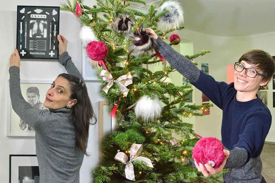 """li.: Die Künstlerin Eleni Trupis (41) hängt ihr Fotogramm """"Desinfectudo"""" (430 Euro) an die Wand. re.: Annette Demski-Klassen (34) mit ihrem Weihnachtsbaum mit Fellbommeln."""