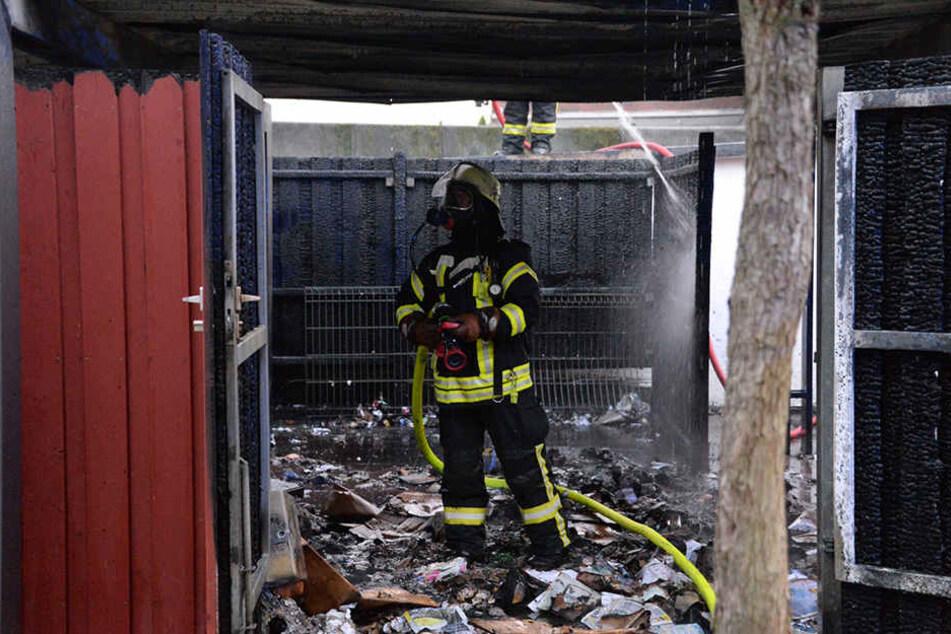 Ein Feuerwehrmann steht in dem völlig verkohlten Carport.