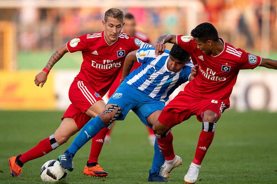 Hamburgs Lewis Holtby (links) und Douglas Santos (rechts) kämpfen mit Erndtebrücks Murat-Kaan Yazar um den Ball.