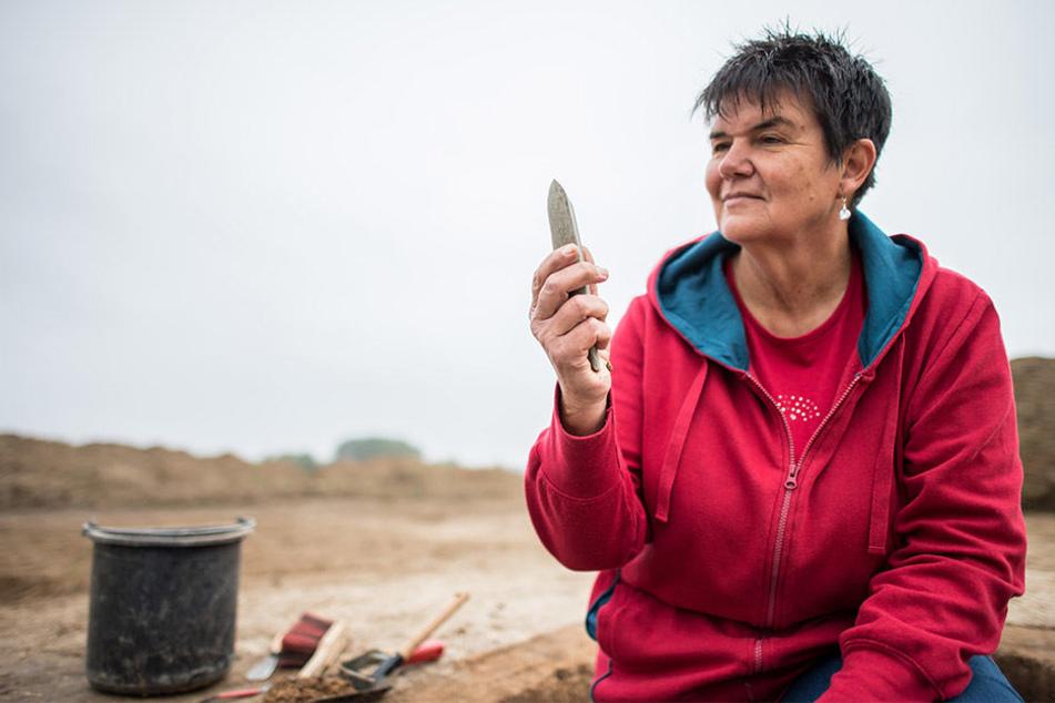 Maria Hahne, Grabungstechnikerin beim Landschaftsverband-Westfalen-Lippe (LWL), begutachtet die Beil-Spitze aus Stein.