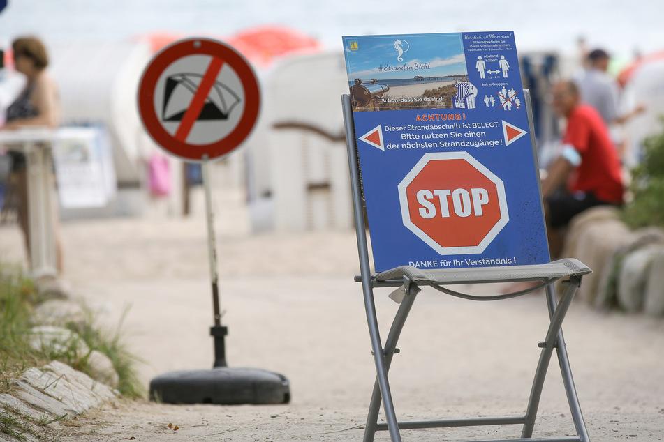 """Ein Stop-Schild und die Aufschrift """"Achtung - Dieser Strandabschnitt ist belegt"""" sind auf einem Hinweisschild an einem gesperrten Zugang zum Timmendorfer Strand zu sehen."""