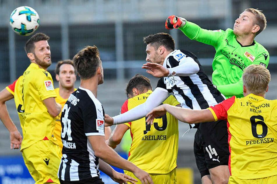 Sandhausens Tim Kister (3.v.r.) und Unions Torwart Jakob Busk (2.v.r.) kämpfen um den Ball.