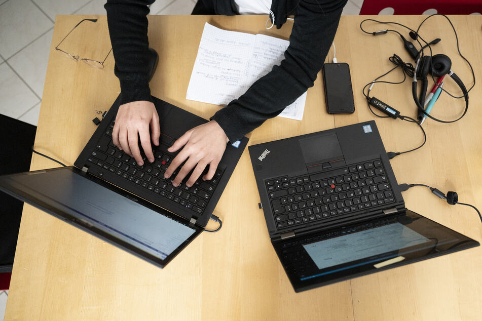 Eine Frau arbeitet an ihren Laptops.