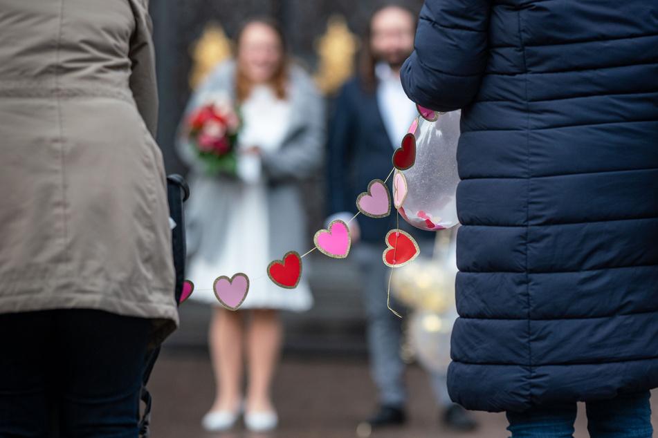 Ein Hochzeitspaar steht in großem Abstand zu seinen Gästen: In NRW ist die Zahl der Eheschließungen im Corona-Jahr 2020 auf einen historischen Tiefstand gesunken.