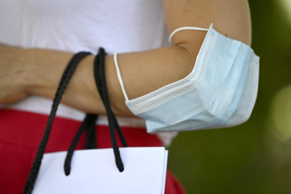 Eine Frau trägt ihre Mundschutzmaske beim Shopping über dem Ellbogen.