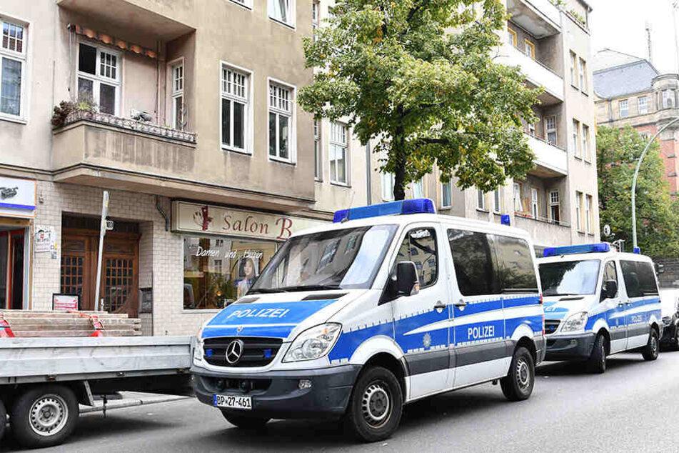 Zwei Streifenwagen der Polizei warten während einer Razzia vor einem Haus. (Symbolbild)