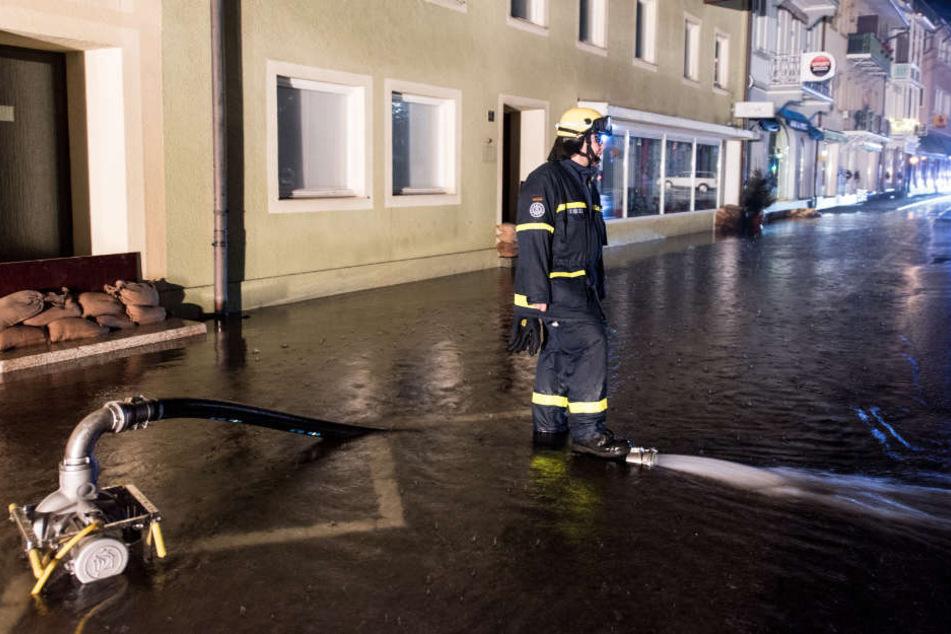 Ein Mitarbeiter des Technischen Hilfswerks pumpt in St. Blasien im Schwarzwald eine überflutete Straße leer.