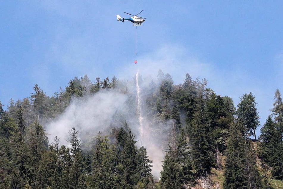 Feuerwehr und Polizeihubschrauber versuchen den Brand bei Oberaudorf unter Kontrolle zu bringen.